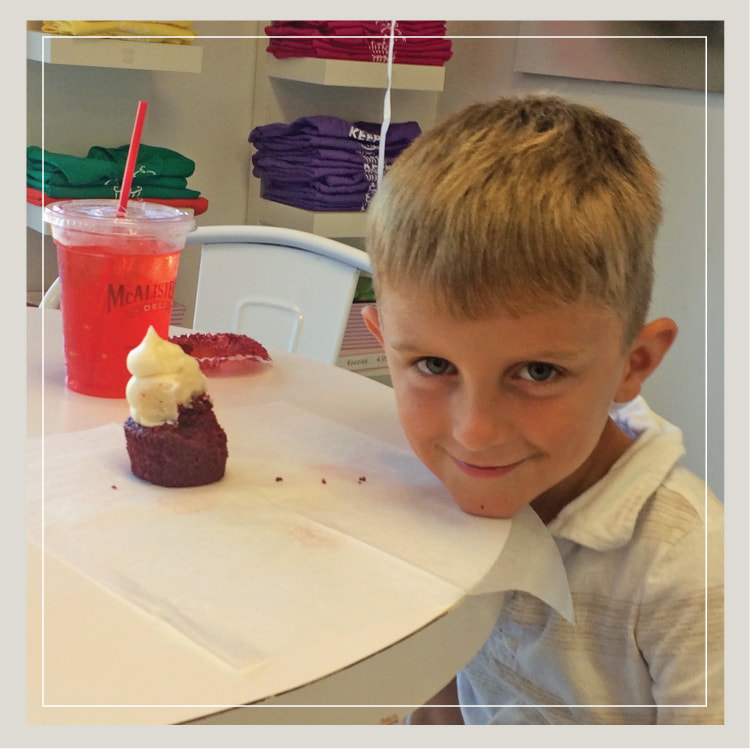 A Birthday Boy Savors Red Velvet Cupcake At Party For Kids
