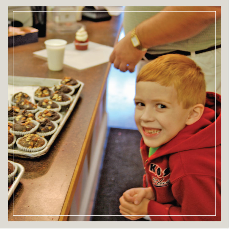 A Boy Smiles In Front Of Row Cupcakes Being Baked And Iced At